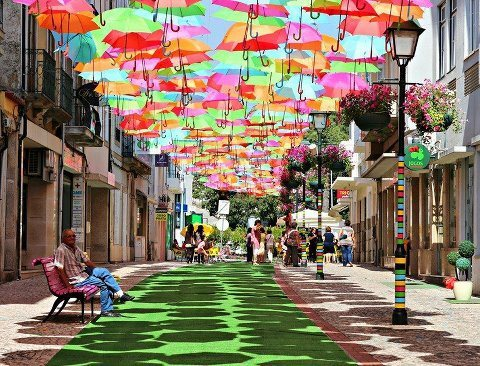 Beautiful street in Portugal, its covered with colorful umbrellas