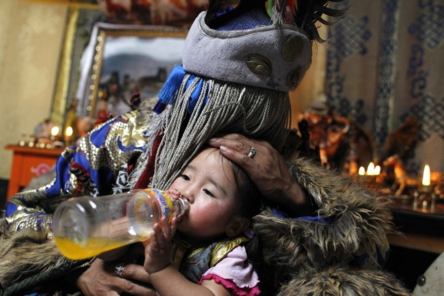 Batgerel Batmunkh, a shaman, kisses his niece Munkhsoyol while 'possessed by the white spirit' during a shamanic healing ritual in their ger on the outskirts of Ulan Bator, Mongolia,