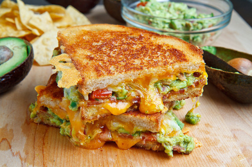 prettygirlfood:  Bacon Guacamole Grilled Cheese Sandwich Ingredients 2 slices bacon 2 slices sour dough bread 1 tablespoon butter, room temperature 1/2 cup jack and cheddar cheese, shredded 2 tablespoons guacamole, room temperature 1 tablespoon tortilla chips, crumbled (optional) Directions Cook the bacon until crispy and set aside on paper towels to drain. Butter one side of each slice of bread, sprinkle half of the cheese onto the unbuttered side of one slice of bread followed by the guacamole, bacon, tortilla chips, the remaining cheese and finally top with the remaining slice of bread with the buttered side up. Grill over medium heat until golden brown and the cheese has melted, about 2-3 minutes per side.  I WANT THIS IN MY MOUTH.