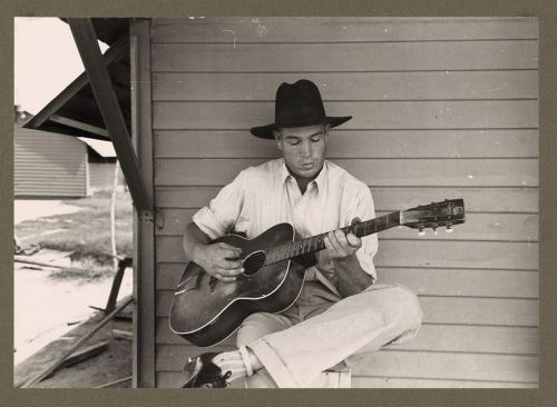 Migratory worker playing guitar on his front porch in Arizona, 1940.