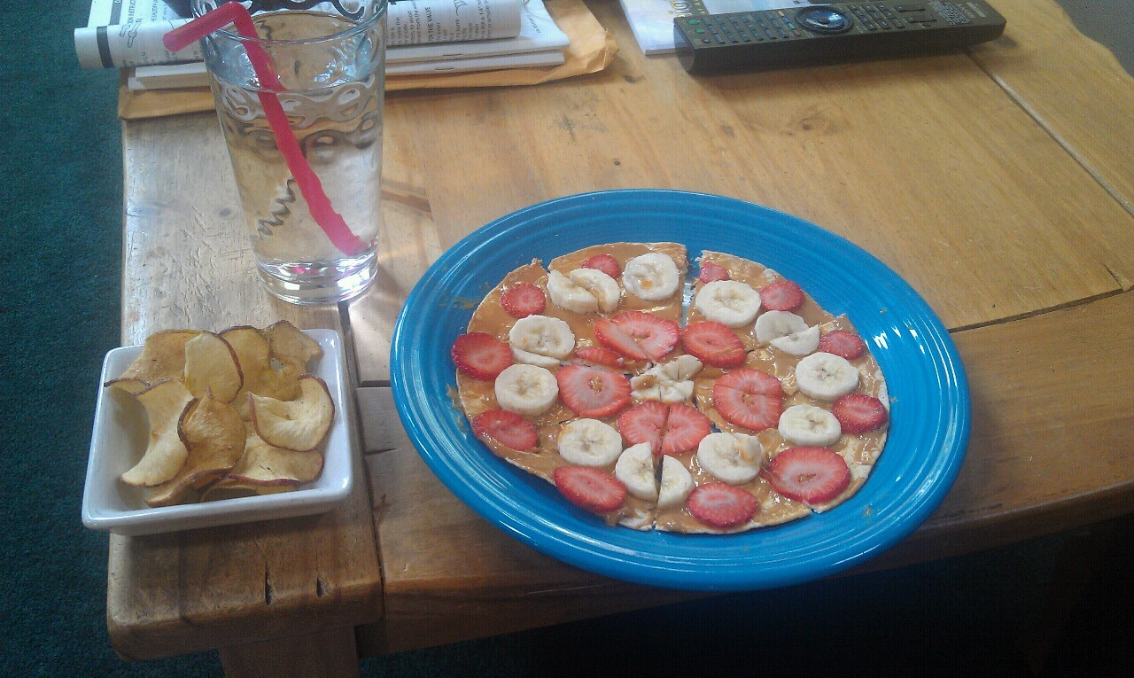 """Pizza"" mockup with peanut butter and strawberries sliced, with apple chips and water"