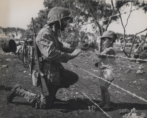 "Marine Shares A Treat, 1944 by Marine Corps Archives & Special Collections on Flickr.Via Flickr: ""Sweet Tooth-A bearded Marine pauses beside the barbed wires of an internment camp on Tinian to give a native child some candy."" From the Photograph Collection (COLL/3948), Marine Corps Archives & Special Collections OFFICIAL USMC PHOTOGRAPH"