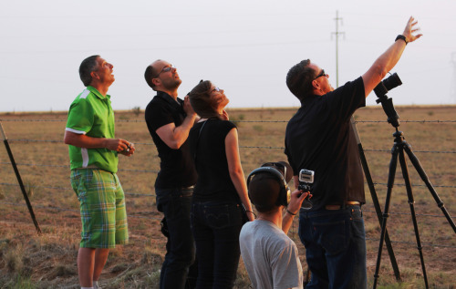 During the 2012 storm chasing season, Roger Hill (far right) explains tornadic activity developing in eastern New Mexico to a group of paying passengers on a Silver Lining storm chasing tour. He uses a collection of technologies when Chasing the Eye of the Storm.