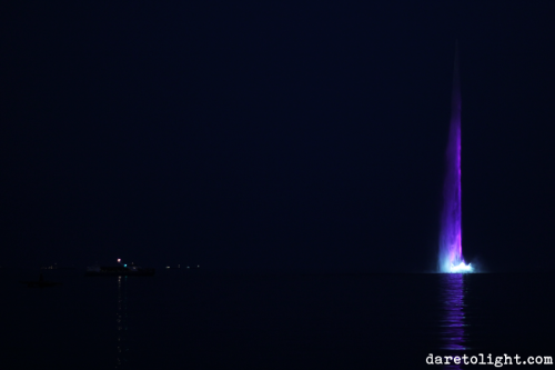 A fountain is strongly lit with two different colours in the middle of the bay to be viewed from the promenade. - in Baku, Azerbaijan
