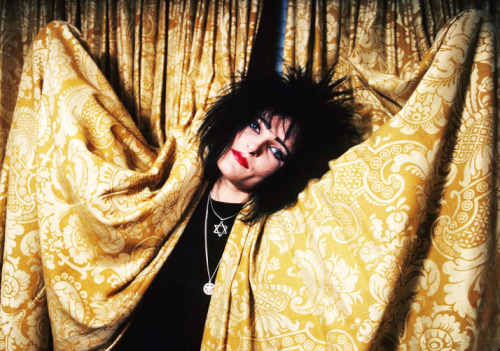 [Siouxsie, peeking through curtains]
