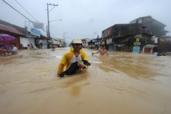 A Filipino man carries a dog through floodwater in Manila, Philippine. At least 20,000 people fled their homes as half the city submerges. August 7, 2012