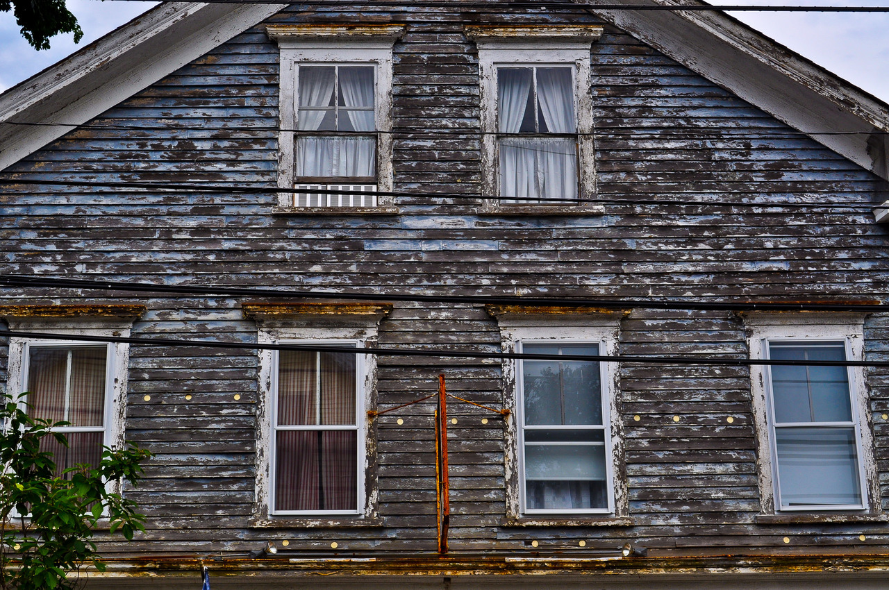 A weathered apartment over an old-fashioned hardware store in New England. I particularly was attracted to the windows and the worn shingles.