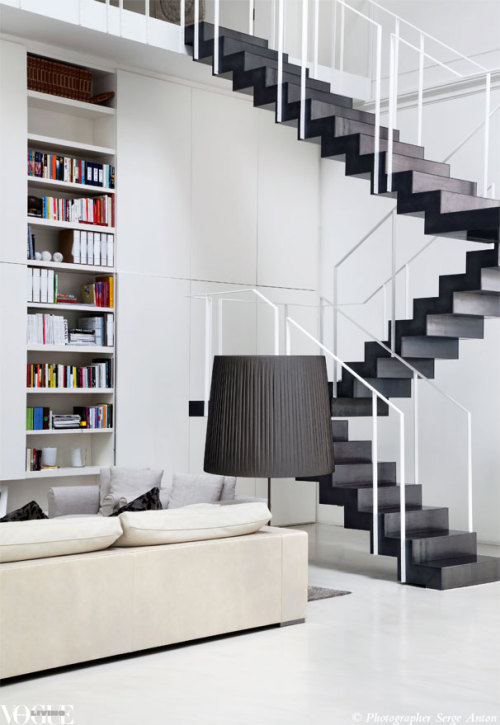 voguelivingmagazine:  A bookcase neatly slots into a wall beneath the graphic laminated steel staircase by Fratelli Ronchetti in this early 1900s theatre-turned-modern-loft by architect Piero Lissoni. From 'Home Theatre', a story on page 166 of Vogue Living July/August 2012, on news stands and Zinio now. Photograph by Serge Anton.