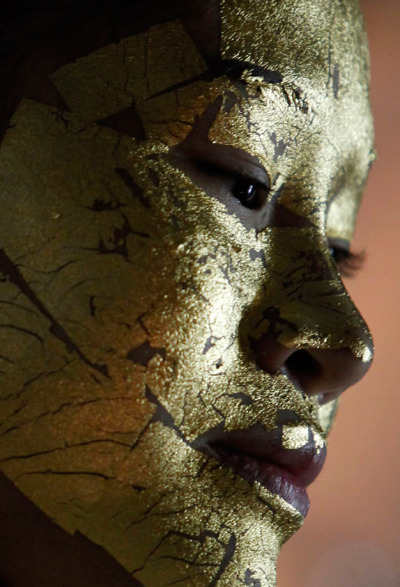A client whose face is covered with gold is seen at the Viet My beauty salon in Hanoi on February 13, 2012. Viet My is one of a small number of salons in Vietnam that provides 24k gold leaf face mask therapy, said to help make skin whiter. A single facial costs 1.8 million Vietnam dong ($86.41). (Kham/Reuters)