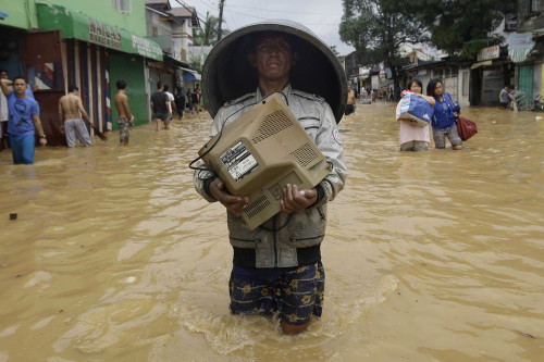 inothernews:  A man carried a monitor through a flooded road in Marikina, east of Manila, Philippines. Widespread flooding that killed at least 23 people, battered a million others and paralyzed the Philippine capital briefly eased on Wednesday. (Photo: Aaron Favila / AP via The Wall Street Journal)