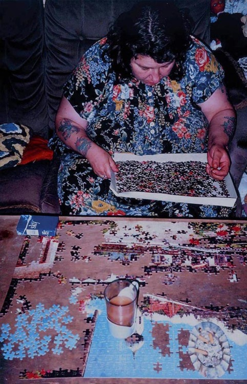 "Liz working on a jigsaw, from the series ""Ray's a laugh"", 1994, by Richard Billingham. ""Ray's a Laugh (book published in 1996) is a portrayal of the poverty and deprivation in which Richard Billingham grew up. The photographs, which were taken on the cheapest film he could find, provide brash colours and bad focus which adds to the authenticity and frankness of the series."" (source) Via Saatchi Gallery."