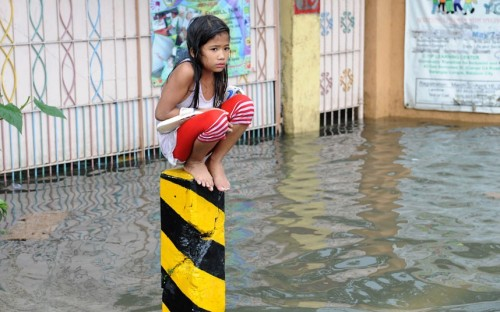 inothernews:  A child sits atop a traffic post on a flooded street in suburban Manila. More than 900,000 residents have been displaced and up to two million people affected throughout a wide swath of Metro Manila and surrounding provinces on the island of Luzon; at least 23 people have died.  (Photo: Jay Directo / AFP-Getty via The Telegraph) Heartbreaking.