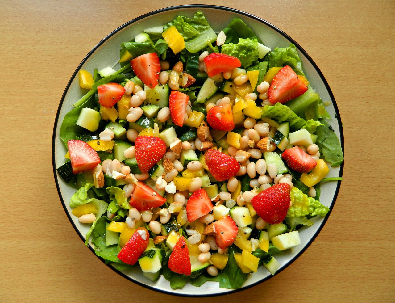 Strawberry and pinto bean salad - Spinach, romaine lettuce, cucumber, courgette, yellow bell pepper, pinto beans, strawberries, chopped almonds, cracked black pepper and a mango and chilli dressing.