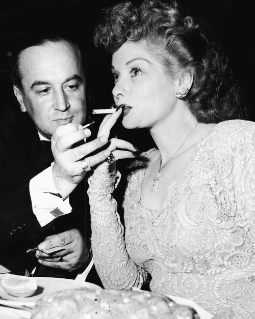 With her eyes glued to the speaker, Lucille Ball receives a light for her cigarette from Jean Negulesco, motion picture director. Daughter of a concert pianist, Lucille started receiving her training for the entertainment world at the ripe old age of five. Years of musical and dramatic coaching have resulted in motion picture stardom for this titian-haired comedienne.Her blue eyes and strawberry-red hair are a combination which makes her a standout in any group. (1947)