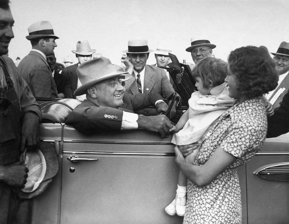 President Franklin D. Roosevelt talks to a young mother while sitting in his car during a trip to the western U.S. in January 1936. By Thomas D. McAvoy