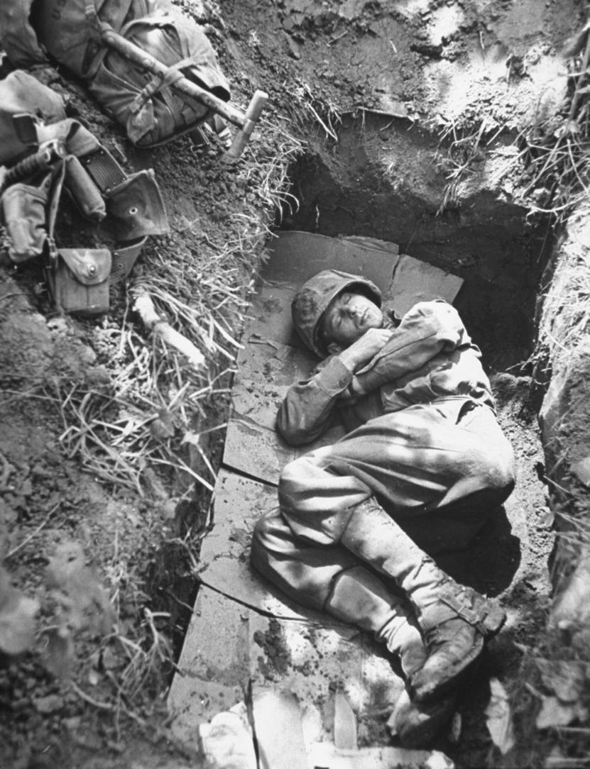 American soldier of a mechanized unit sleeping in a foxhole lined w. cardboard after long grueling march through rugged mountains.  Photo by George Silk. Italy, 1944
