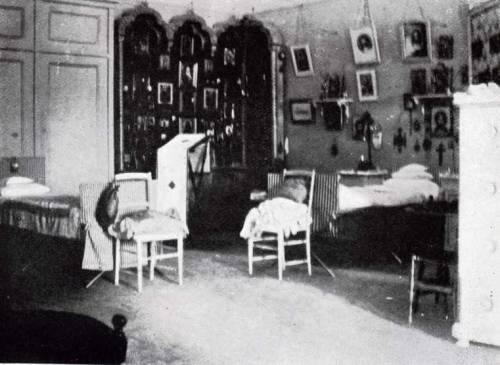 Anastasia and Maria's Bedroom.  What I can tell you about this picture is that this is how their bedroom looked back when they lived there. Maria and Anastasia's Bedroom was next door to their sister's. It was very similar in style, except the frieze in this room showed butterflies in roses stenciled above gray-painted walls. It was also slightly larger than that of their older sisters. Anastasia and Maria's bedroom did not have a doorway to the hall, so the first thing that is notably different in their room compared to the big pairs is the giant closet on the back wall. Secondly, the display they used to hold their icons had peaks of even height, whereas the big pair's was staggered. Maria's bed laid against the back and side walls (left), while Anastasia's bed is the one coming off the side wall (right). The room was decorated in green and white and had a dressing table against the window. The mattresses on the camp beds were thin and were covered with two blankets, which were adorned with the girls' initials. As the girls grew older, they began to decorate their sides of the room to their taste by covering the walls in framed photos from their various outings, paintings, portraits, and whatever else fit their fancy. Icons covered the rest of the walls as the girls were highly religious.