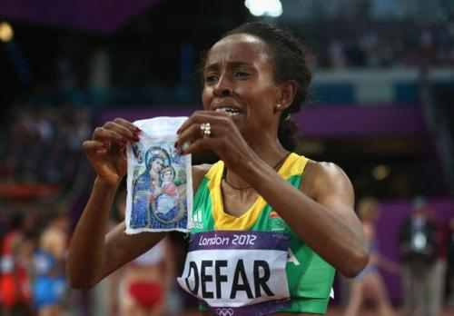 joecatholic:  Ethiopian athlete Meseret Defar provided one of the most emotional moments of the London 2012 Summer Olympic Games when she crossed the finish line in the 5000 meter race to win the gold. She then pulled a picture of the Virgin Mary out from under her jersey, showed it to the cameras and held it up to her face in deep prayer. An Orthodox Christian, Defar entrusted her race to God with the sign of the cross and reached the finish line in 15:04:24, beating her fellow Ethiopian rival Tirunesh Dibaba, who was the favorite to win.