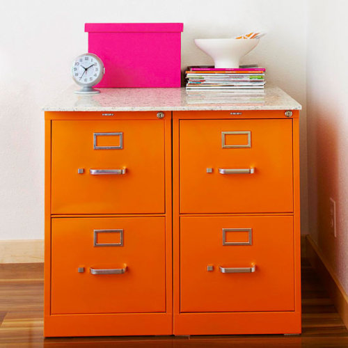 Add a bold pop of color to your filing cabinets with spray paint. Tape off the hardware (handles, lock, etc.) or remove them before painting. Set two filing cabinets side-by-side and add a table top. Cut wood or stone to fit both tops.