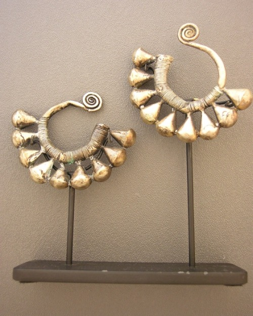 "China | These large silver ""earrings"" were made in by the Miao people in Guizhou Province, China. In the olden days, the Miao would melt down silver coins to make their jewelry, since their provinces had almost no silver that could be mined from the ground."