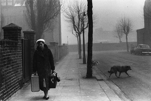 Bert Hardy Journalist Katharine Whitehorn carries her luggage along a foggy London street,1956