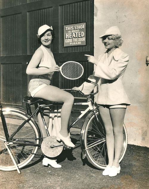 Louise Allen rides a bike, holds a racket. Victoria Vinton points.