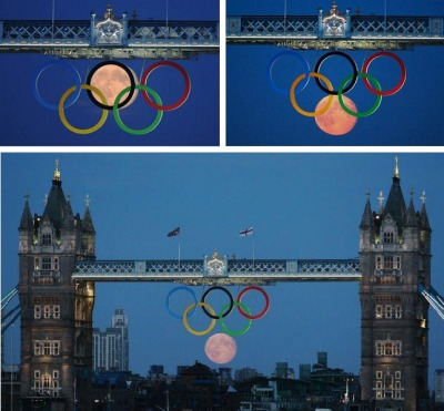 The moon rises between the Olympic Rings below the Tower Bridge in London