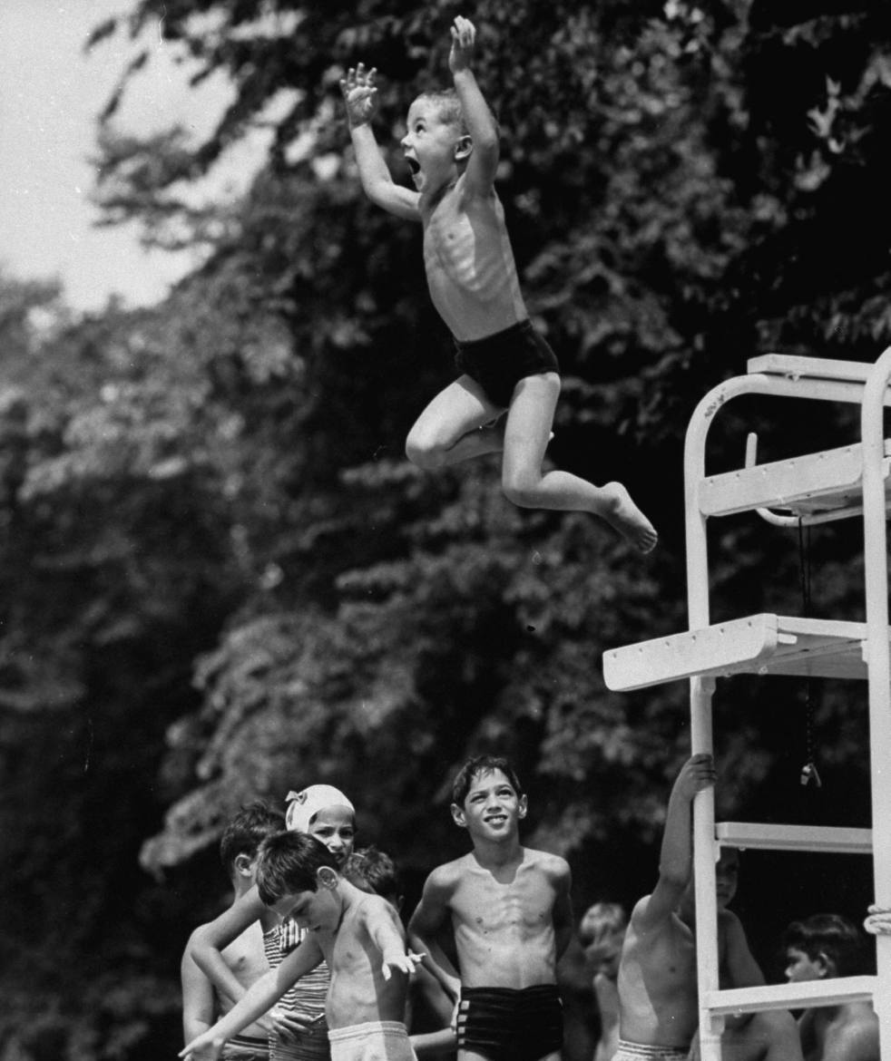 silfarione:  Children at Glen Echo amusement park pool waiting their turn while boy is leaping from diving board into water below.  Photo by Mark Kauffman. 1953