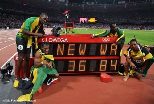 olympics:  Usain Bolt, Yohan Blake, Michael Frater and Nesta Carter of JAM celebrate next to the clock after winning gold and setting a new world record of 36.84 during the Men's 4 x 100m Relay Final