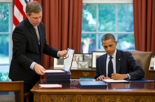 President Barack Obama signs a bill into law at the Resolute Desk in the Oval Office, Aug. 10, 2012. Staff Secretary Doug Kramer, left, prepares the next bill for the President's signature. (Official White House Photo by Pete Souza)
