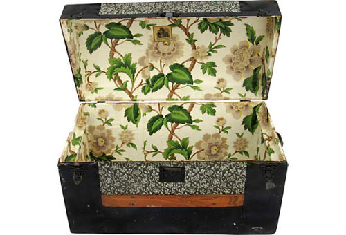 Gorgeous dome-top trunk with Art Nouveau pressed-tin floral inserts and a floral wallpaper-lined interior. Black tin, wood slats, and hardware adorn and protect the exterior. Original latches. Handle missing on left side, but hardware remains for replacement. Tiny wheels embedded in the wood slat base. Available now in the Furniture Collection by Ruby + George.