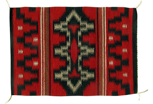 Fine deep red Ganada Navajo rug woven by Leonora Benally with traditional geometric design. Cream tassels at all four corners. circa the 1970's.