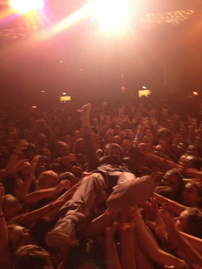 fishingboatproceeds:  This is a photo of me stagediving at LeakyCon. It was taken by the lovely and charming Evanna Lynch. Life is weird/beautiful. Anyway, while I was crowdsurfing—I was out there for quite a while—I had time to think about some things: 1. The Harry Potter fandom is uniquely wonderful, and the greatest luck of my professional life is probably that so many HP fans became early nerdfighters, because the whole culture of nerdfighteria came not primarily from us but from those early nerdfighters. 2. Although it is hard for me to express it in a meaningful, individual way, I am really grateful to everyone who identifies as a nerdfighter. We've done so much amazing stuff together that none of us could ever have done alone. 3. I love being a nerdfighter, and I love being a nerd, and I seeing people be so honestly themselves is such an inspiration to me. 4. How are all these people—many of whom are very small—holding me aloft? 5. The metaphor here is too obvious. 6. There's probably a better, more interesting metaphor that I'm not thinking of. 7. I guess the real metaphor is not you-can-only-make-stuff-if-people-hold-you-up; the real metaphor here is that together-things-happen-that-can-never-happen-alone, which is a very important thing for an introverted and socially anxious person like me to realize. I guess these days this is a politically charged statement, but it seems to me manifestly true: You make nothing alone. Human beings are not mere competitors, and human life is not merely competition. We are collaborators. To be human is to catch the falling person.  Only John Green would be stagediving and start getting metaphorical.