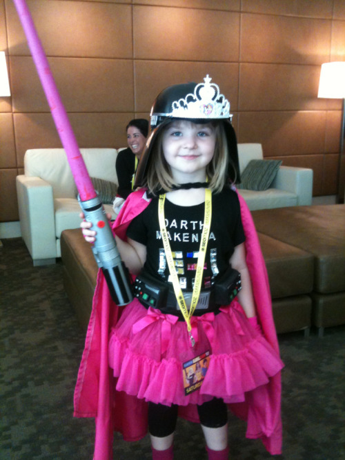 alienfirst:  theprinceofgay:  And of course the cutest little geek. She came over to me when I was sitting around and talked about my boots, and we ran into each other all around the con. I ended up giving her my favourite Princess Celestia pin that I had gotten a few cons back. The look on her face when I pinned it on her badge told me she'd treasure it a lot more than I did, haha.  This little girl is the best cosplay. Bestest. Everyone else can go home. My fiance and I were just giggling after she came by our table.  Really though, how much more perfect can you be? (The tiara also lit up.)  Darth Makenna for President