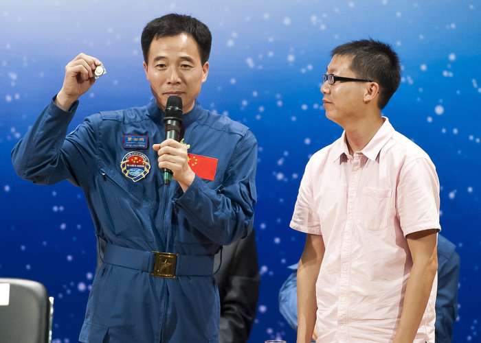 HONG KONG: Aug. 12, 2012 — Wearing blue jumpsuit, astronaut Liu Wang (left) presents a souvenir pin to a university graduate during a seminar sharing their space experience with university students in Hong Kong Sunday, Aug. 12, 2012. (Photo by JUSTIN CHIN)