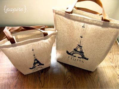 Paris Waxed Canvas Bags Sizes: Small | Large  <Small> Dimension: 29(L)*22(H) cm ; Base: 15(L)*15(W); Handles: 12cm (H) <Large> Dimension:   30(L)*32(H) cm ; Base: 22(L)*9(W); Handles: 12cm (H) Waxed Canvas bags Waterproof lining on the inside Zakka influenced style  Silkscreen printed graphic of the Eiffel Tower on the front PVC Handles Small Bag comes with a Pouch on the inside Large Bag fits A4, Great for carrying books and documents  Small: SGD$8.00 each Large: SGD$12.00 each  Detail:
