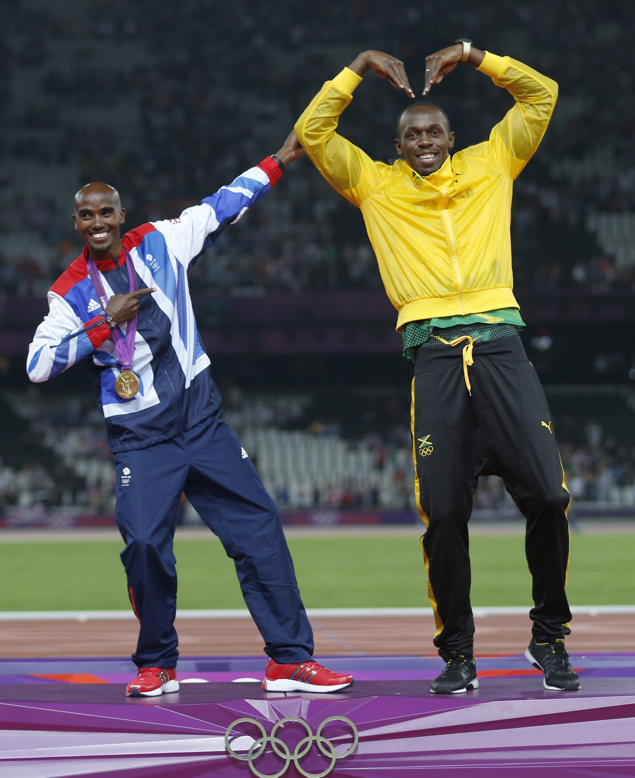Jamaica's Usain Bolt (R) celebrates with Britain's Mo Farah on the podium after each receiving gold medals, Bolt for men's 4x100m relay and Farah for men's 5000m at the victory ceremony at the London 2012 Olympic Games at the Olympic Stadium August 11, 2012. REUTERS/Eddie KeoghFULL COVERAGE: The London 2012 Summer Olympic Games