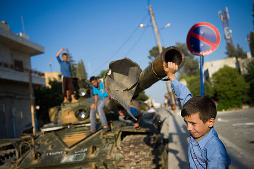 August 12th, 2012 in Azaz, Syria: Boys play on a tank. Syrian forces shelled rebels in the battle-scarred Aleppo and blasts rocked Damascus, as US secretary of state Hillary Clinton called for an acceleration of the regime's downfall.