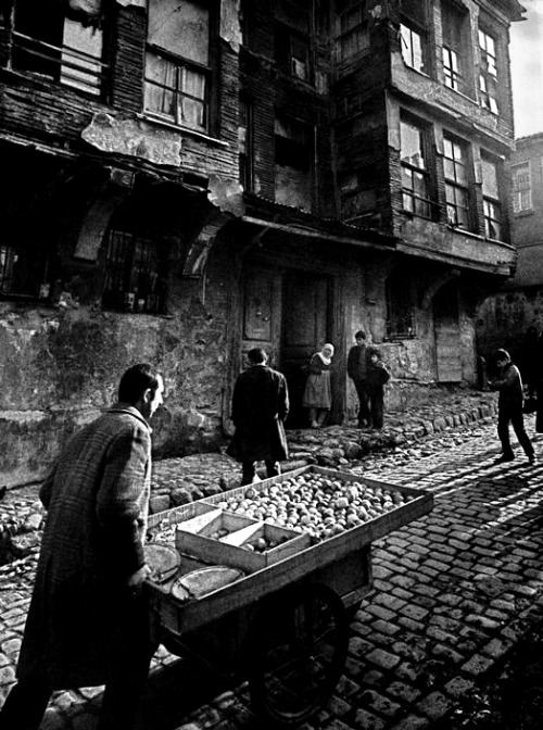 costermonger in a street in zeyrek, 1959 photo by ara güler, from ara güler's istanbul can't take my eyes off the man with his back to the camera.
