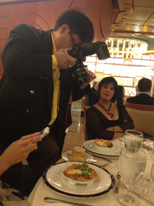 My dad taking a picture of his meal during our cruise vacation.