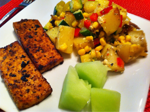 "Holy Mole Tofu, Warm Potato & Veggie Salad with Feta, and Honeydew Melon. I rubbed the extra-firm tofu slices with Holy Mole Chef Salt and refrigerated them in a marinade of the following: Sesame Oil Lime infused Oil Black Currant Vinegar Bragg Liquid Aminos Honey and Organic Minced Ginger Then I fried the tofu in coconut oil. For the warm potato and veggie salad, I fried gold potatoes in butter with cracked pepper and Himalayan pink salt. Sautéed the zucchini and red pepper in olive oil with cracked pepper and the same salt. I combined the potatoes, zucchini, red pepper, and a can of organic sweet corn. I let the salad rest and cool a bit then drizzled it with melted butter and lemon juice and added tomato-basil feta and tossed. I served the tofu and salad with honeydew melon. My husband said, ""this tofu is the bomb!"". Always a good thing to hear about tofu. ;-) He suggested that I make the same marinade for chicken to put on the grill. The warm salad was an adaptation from a recipe that my friend Amy found on FoodGawker. That recipe called for green beans, fresh corn, and potatoes with feta. I gave it a shot with what I had and it worked! Yummy. :D"