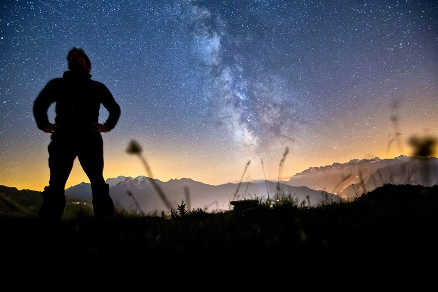 A man looks for meteorites while standing on the Col du Tronc path above Verbier, Switzerland on Aug. 10, 2012. The Mont Blanc massif mountain range lies in the background of this one-second-exposure photograph. [Credit : Alessandro Della Bella / EPA]
