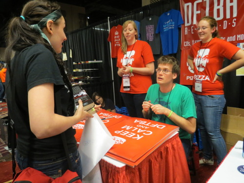 "valerie2776:  dearpadfoot:  This is the story of how I met John Green.  I was walking through the vendor room, minding my own business- and mind you, my bag was full to the brim, not only because I had purchased many things from the vendor room, but also because I had been carrying around my complete set of John's collective works hoping to run into him- when all of a sudden I see a familiar face sitting at the DFTBA table.  Yes, John was sitting there and he was signing posters in a true and speedy fashion. So, of course, I awkwardly walk up to the table, arms laden with the books I had just managed to pull out of my bag as well as all of the things I had just come out of the Starkid signing with, which happened to include a brilliant silver sharpie.  Just as I approach the table, John tells the person behind him that he needs a silver sharpie. LO AND BEHOLD WHAT DO I HAVE IN MY HAND?! A SILVER SHARPIE. So, of course, I awkwardly say, ""I have a silver sharpie…"" as I hold it out to him. He offers me five dollars for it. I push him my stack of books. This picture is representative of our symbiotic relationship. We were in awe that life worked out so well. He needed my marker and I needed his signature. And so now I have a complete set of signed and personalized John Green novels!  oh man, lindsay, katy, and i are gonna be in the background of so many leaky pictures. this was a really cute and good moment! hooray for silver sharpies and bartering!  I want to see some where we successfully photo bombed with just Pizza John's face and not our own. I loved this moment too :)"