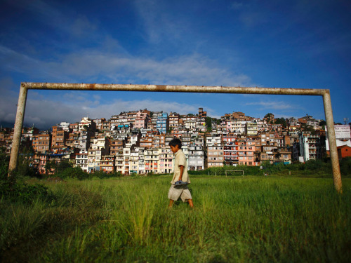 guardian:  A boy walks past a football goal near the ancient city of Kirtipur Photo: Navesh Chitrakar