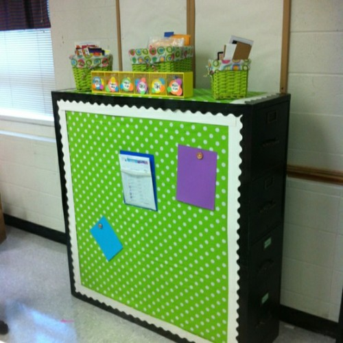 classroomcollective:  Two filing cabinets back to back with fabric to cover = magnet board