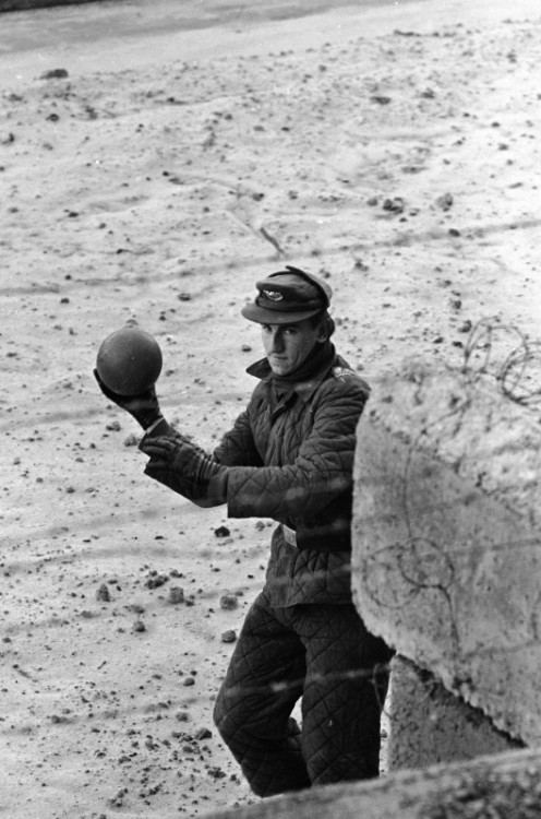 An East German border guard tosses a ball back over the Wall after a West German child mistakenly threw it over. Berlin, 1962. Paul Schutzer