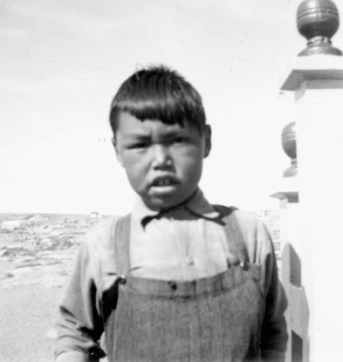 An unidentified Inuit boy wearing overalls [Casimir Kriterdluk] [graphic material]. Chesterfield Inlet, N.W.T., [Chesterfield Inlet (Igluligaarjuk), Nunavut], 1951? Credit: Fleurimond Constantineau / Library and Archives Canada / e004665254 Restrictions on use: Nil Copyright: Estate of Fleurimond Constantineau Title of the photograph in square brackets is based on information provided by Project Naming. This project brings Youth and Elders in Nunavut to work together to identify and record the names of people in photographs held at Library and Archives Canada. Source