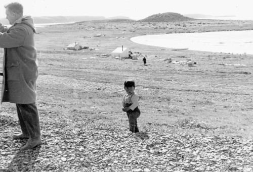 Unidentified Inuit toddler standing behind a white male. Frobisher Bay, N.W.T., [Iqaluit (formerly Frobisher Bay), Nunavut], 1965 Credit: Jean Beetz / Library and Archives Canada / e004665264 Restrictions on use: Nil Copyright: Estate of Jean Beetz Series title: Voyage dans le Grand Nord canadien, 196 Source