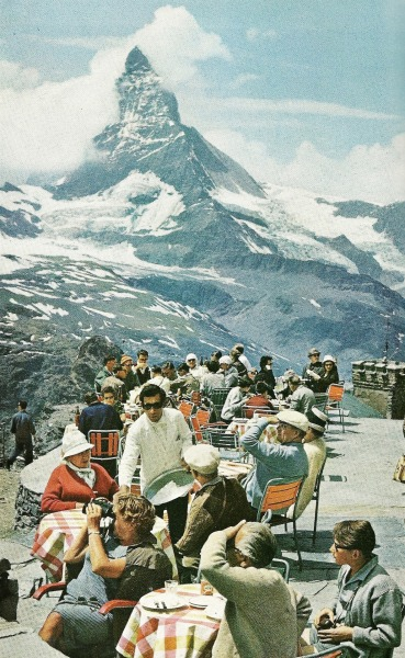 Tourists lunch on the terrace at Gornergrat Station, Switzerland. The Mattherhorn, one of the highest peaks of the Alps, snags a cloud in the distance. National Geographic | September 1965