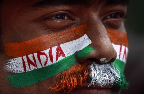 An Indian man, with his face painted in colors of the Indian flag, attends the rehearsal for the Indian Independence Day celebrations in the eastern Indian city Bhubaneswar, India.